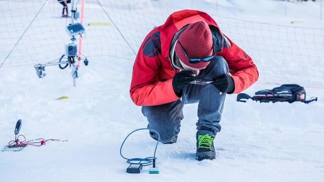 Ein Mann untersucht Schnee unter der Lupe
