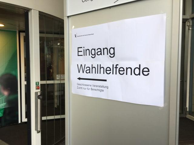 """Plakat mit Pfeil und der Aufschrift """"Eingang Wahlhelfende""""."""