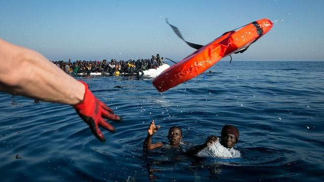 Ein Arm mit rotem Handschuh wirft zwei im Meer treibenden Flüchtlingen eine Schwimmweste zu.