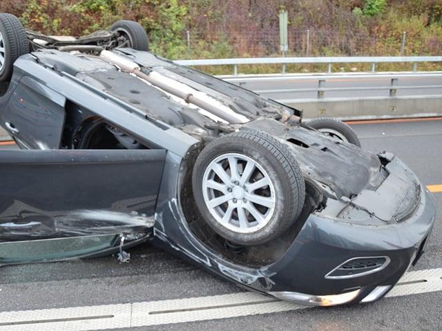 Unfallauto liegt auf dem Dach auf der Strasse.
