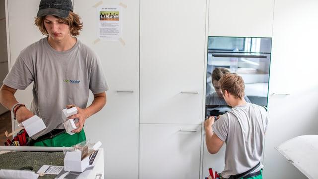Zwei Elektriker-Lehrlinge der CKW Conex bei Montagearbeiten in einer Küche in Kriens.