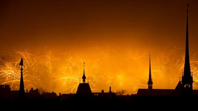 Ein Nachthimmel mit Kirchtürmen und einem verschwommenen Feuerwerk.