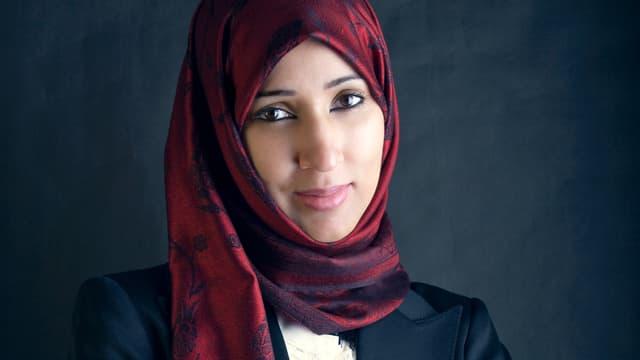 Manal al-Sharif trägt ein rotes Kopftuch und lächelt in die Kamera.