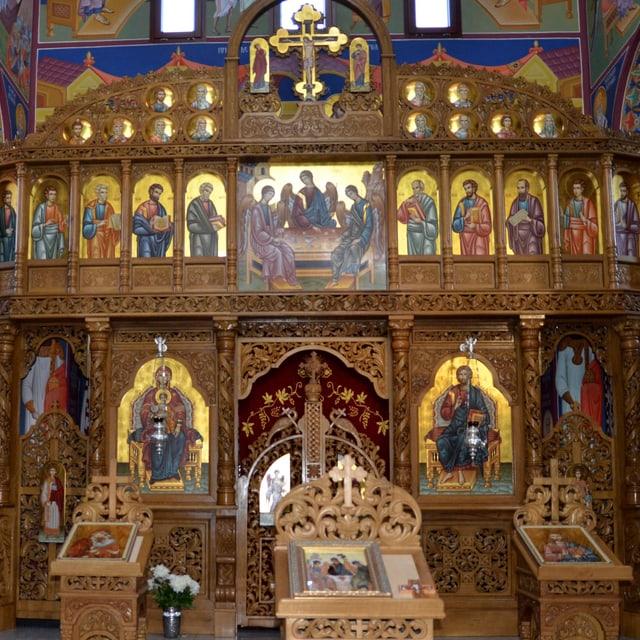 Die Trennwand zum Altarraum ist bemalt und mit Schnitzereien verziert.