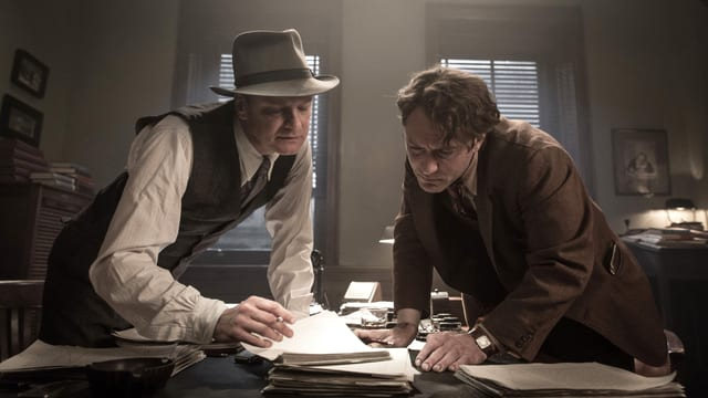 Zwei Männer beugen sich über Papier, das auf einem Schreibtisch liegt.