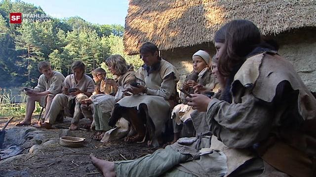 Pfahlbauer sitzen am Feuer und essen.