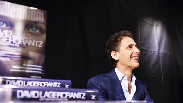 Der Autor sitzt lächelnd an einem Pult. Das Cover seines Buches ist neben ihm zu sehen.