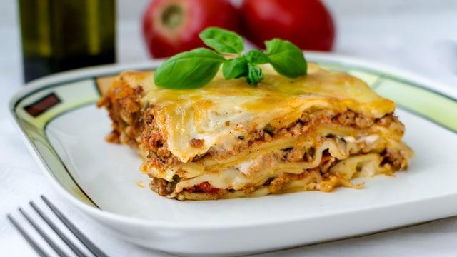 Teller mit einer Portion Lasagne.