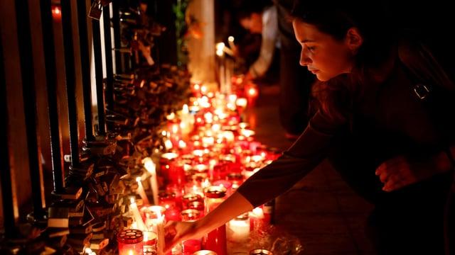 Eine Frau zündet eine Kerze an, hunderte weitere Kerzen brennen bereits.