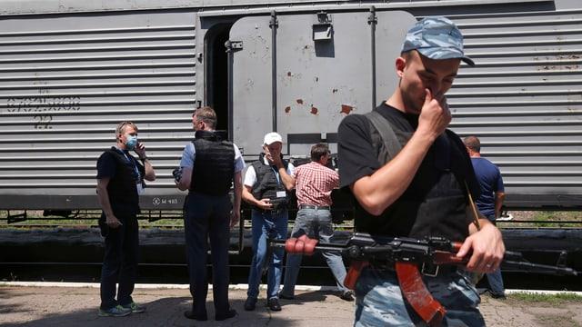 OSZE-Beobachter und Separatisten vor einem Kühlwaggon - sich die Nase zuhaltend.