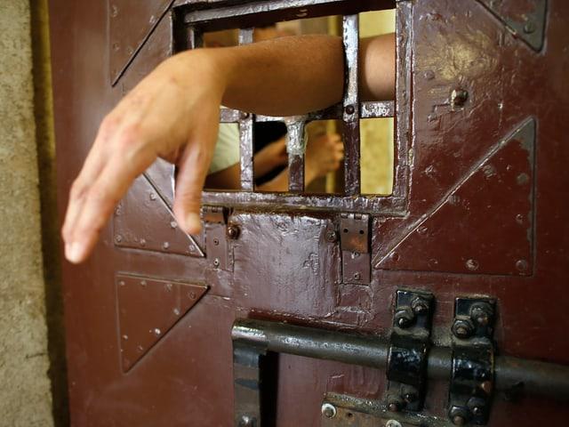 Eine Hand wird durch ein Gefängnisgitter gestreckt.