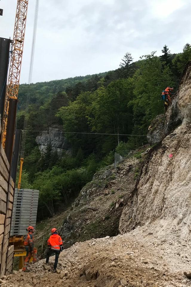 Kletterer an Felswand bei Baustelle.