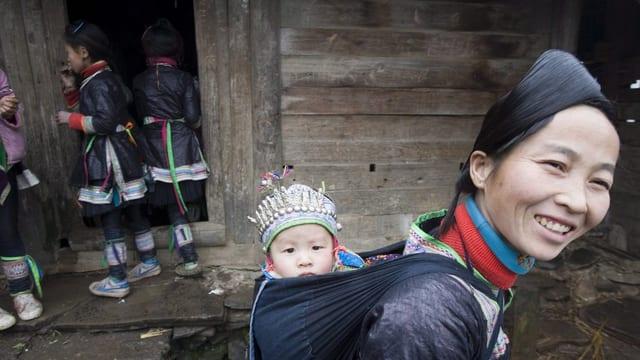 Eine Frau und Kinder der Dong, in traditioneller Kleidung