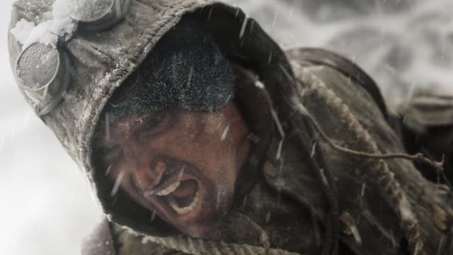 Ein Bergsteiger schreit in einem wilden Schneesturm.