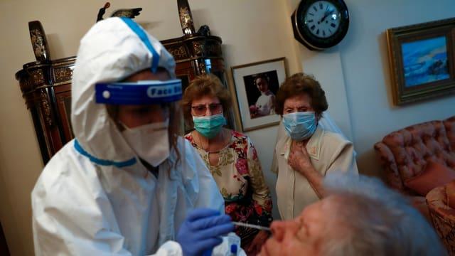 Eine Pflegende testet eine Seniorin auf das Coronavirus.