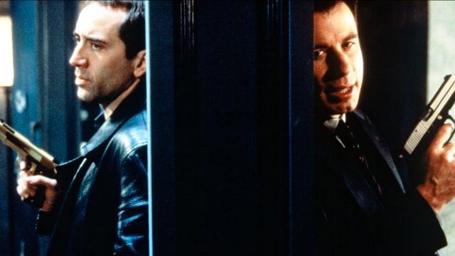 Zwei Männer stehen auf der jeweils anderen Seite einer Wand. in den Händen halten sie je eine Handfeuerwaffe.