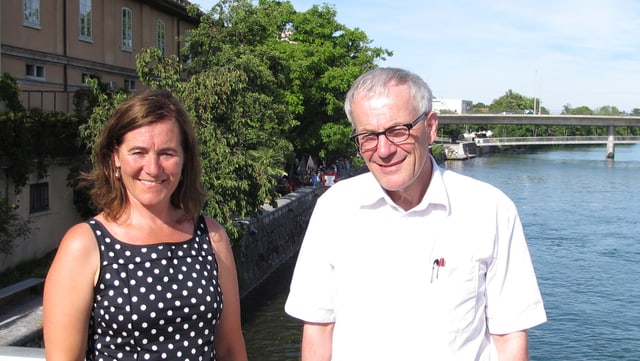 Zwei Personen stehen auf einer Brücke, dahinter ein Fluss