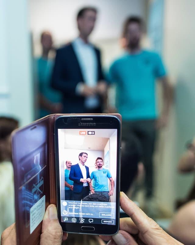 Durch einen Smartphone-Bildschirm sieht man Sebastian Kurz mit einem jungen Mann sprechen.