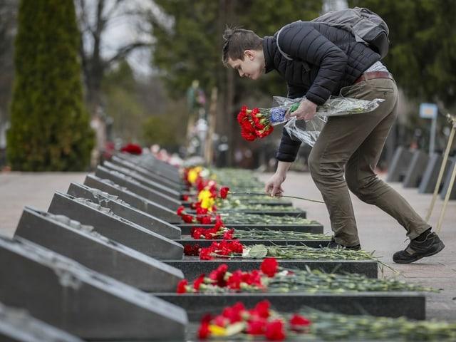 Ein Mann legt Blumen auf Gräber