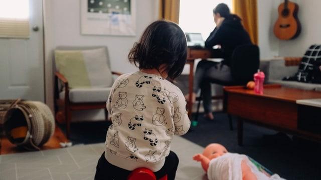 Kind spielt im Vordergrund. Mutter im Hintergrund am Laptop.