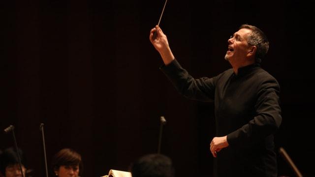 Der Dirigent bei der Arbeit, er hebt mit der rechten Hand den Takstock und blickt konzentriert in sein Orchester.