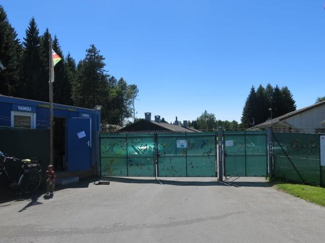 Ein blauer Baucontainer steht vor einem grossen Zaun mit grünem Sichtschutz.