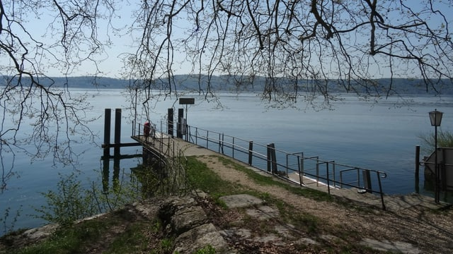 Ein Pier am auf einer Insel in einem See. Die Sonne scheint.