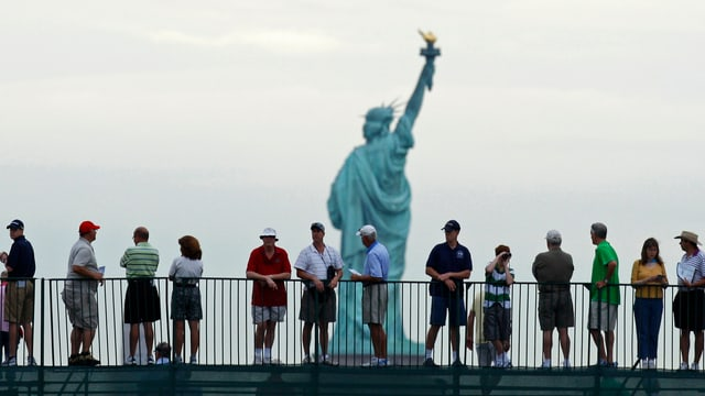 Touristen bewundern von Weitem die Freiheitsstatue in New York.