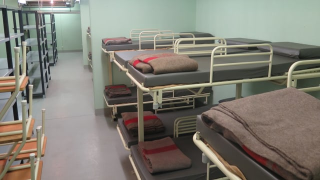 Bunkermässiges Zimmer mit Doppelstockbetten, auf denen Armeewolldecken liegen.