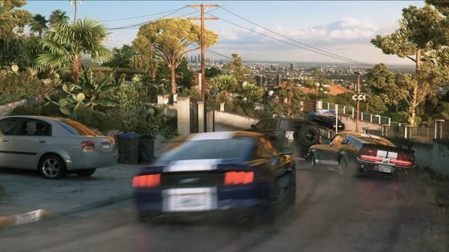 Autos rasen eine enge Strasse hinunter.