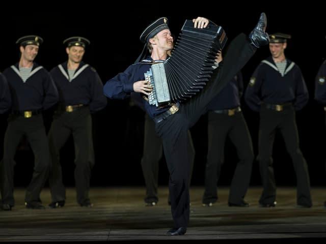 Ein Tänzer in Matrosenuniform hält eine Handorgel in der Hand und tanzt dazu.