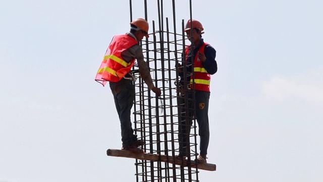 Zwei Bauarbeiter arbeiten an einem Eisengerüst.