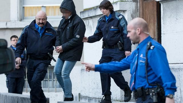 Polizisten führen die Frau in Handschellen ab.