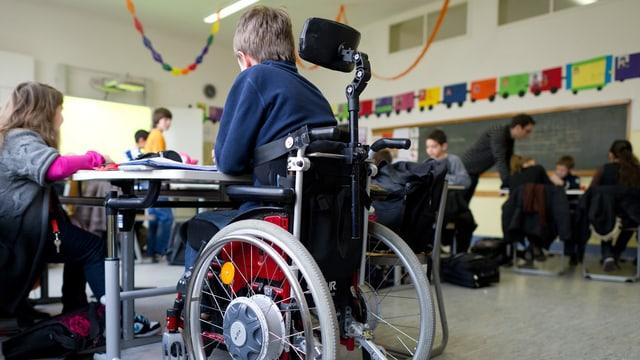 Bub sitzt in Rollstuhl in Schule