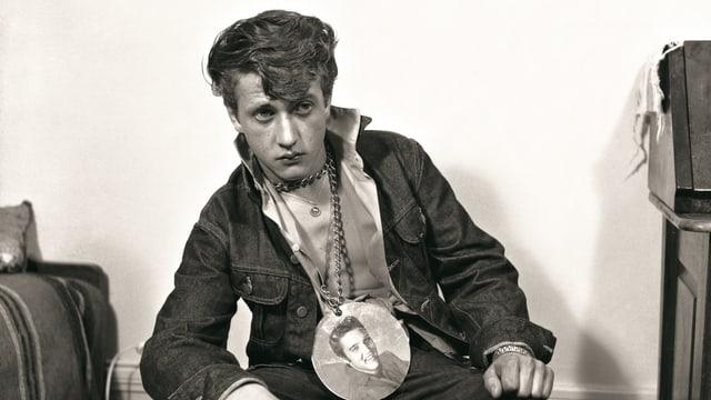 Mann sitzt auf Sessel mit Elvis-Plakette um den Hals