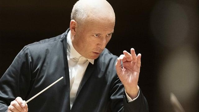 Mann Mittleren Alters dirigiert mit Dirigentenstab in der Hand