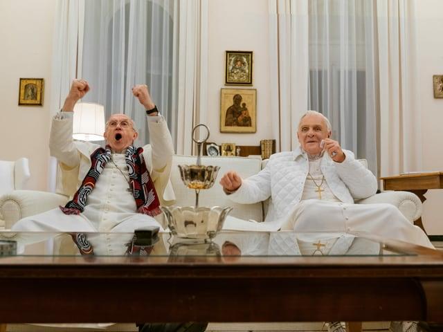 Zwei Päpste sitzten auf einem Sofa und jubeln.