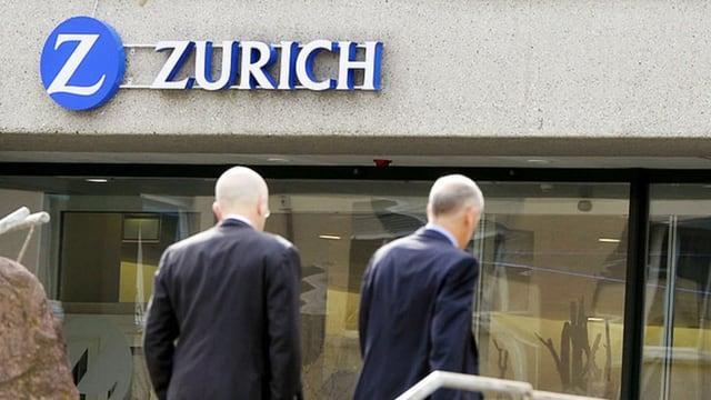 Duas persunas avant l'entrada da l'assicuranza Zurich.