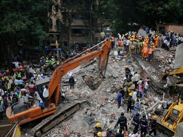 Bagger und schwere Baumaschinen auf Trümmerhaufen.