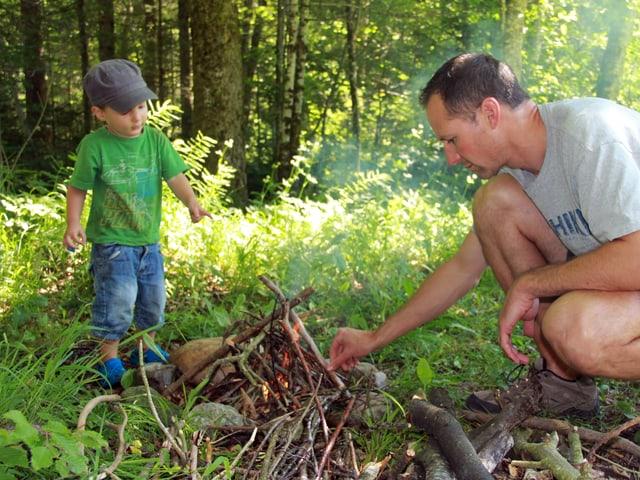 Kleiner Bub und Mann machen ein Feuer im Wald.