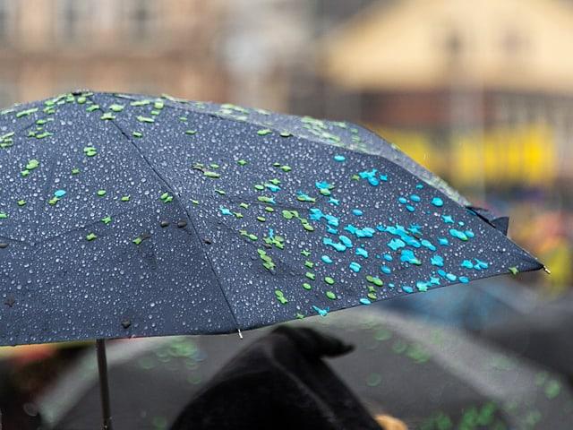 Schwarzer Regenschirm, der aufgespannt ist. Darauf kleben kleine, farbige Papierstückchen in grün und blau.