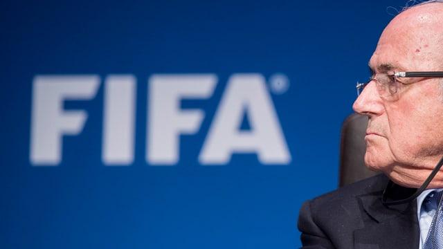 Sepp Blatter che guarda da la vart en. Davossiers  il logo da la FIFA.
