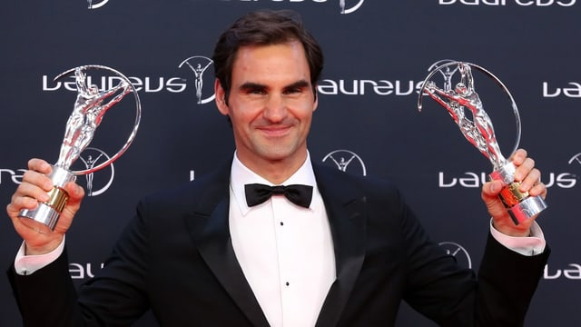 Purtret da Federer cun enta maun duas da las trofeas.