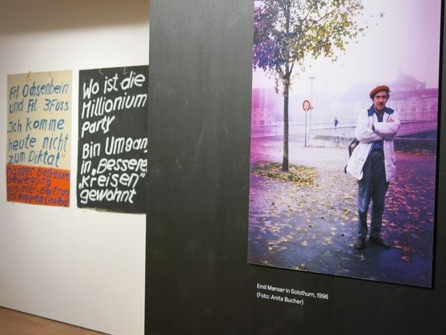Ein Bild von Emil Manser, im Hintergrund zwei seiner Plakate