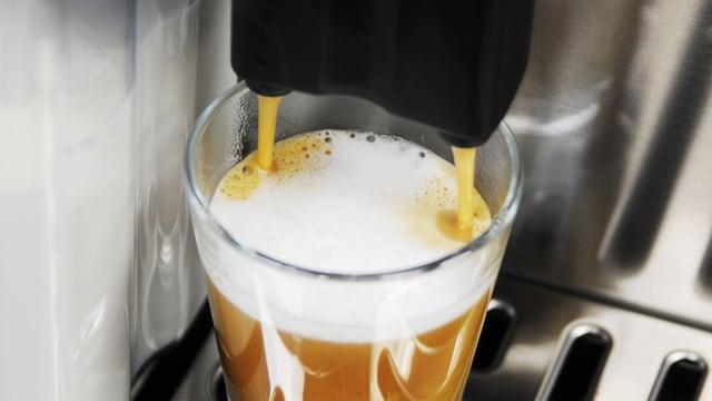 Kaffeevollautomat füllt ein Espresso-Macchiato in ein Espressoglas.