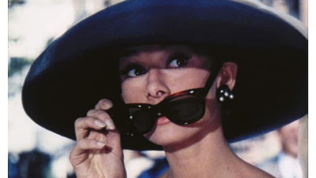 Frau mit grossem Hut und Sonnebrille.