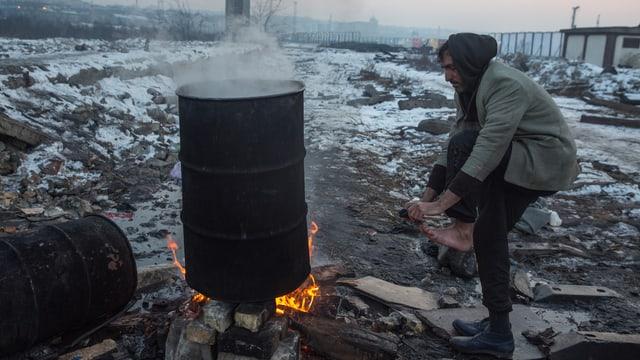 Ein Flüchtling in einem wilden Camp am Belgrader Bahnhof wärmt sich draussen in der Kälte an einer improvisierten Feuerstelle (Eine Tonne über einem Holzfeuer)