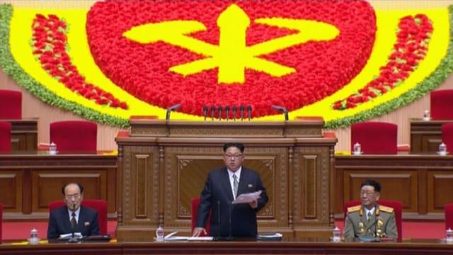 Kim Jong Un an einem Rednerpult hinter einem Emblem der Partei.