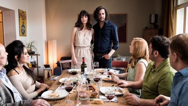 Eine Frau und ein Mann stehen vor einem Tisch, um den weitere Personen sitzen.