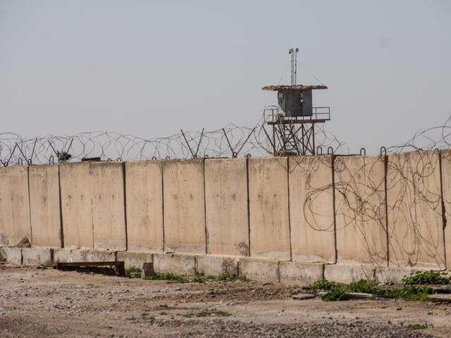 Eine Betonmauer gesäumt von Stacheldraht in der Wüste. Dahinter ein Wachturm.